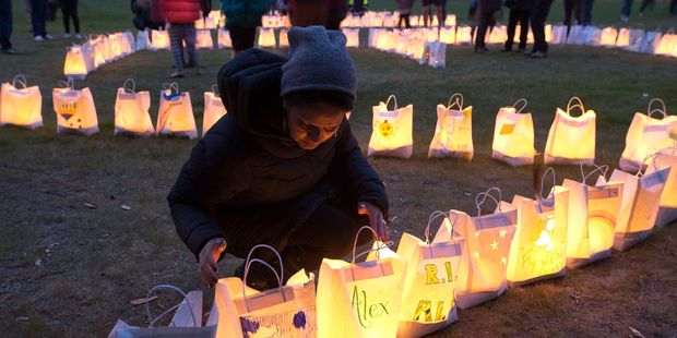 Maria Lyne, a teacher from Levin's St Joseph's School, viewing candle-lit paper bags during the vigil at the Waitarere Domain. Photo / Mark Mitchell