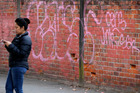 EYESORE: A woman checks her phone in an alleyway littered with graffiti, off Dalton St, Napier. PHOTO/Duncan Brown