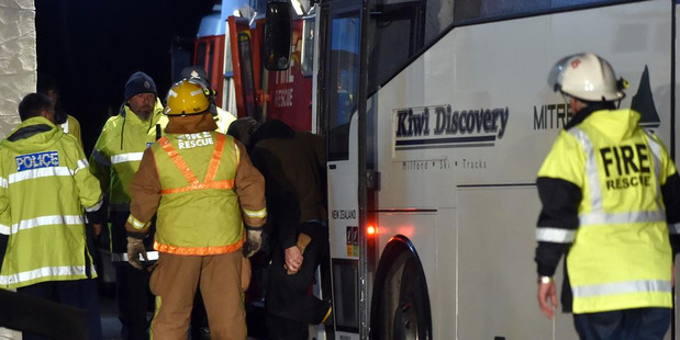 Some of the group are escorted from the bus that delivered them to the Roxburgh Rugby Club after the rescue. Photo / Otago Daily Times / Peter McIntosh