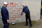 Far North Mayor John Carter (right),  with Walter Te Huia, helps paint over graffiti before the opening games at Lindvart Park's revamped netball courts. Photo / Mike Edmonds