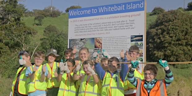 """The children from Maungaturoto Primary School celebrate the unveiling of a """"Welcome to Whitebait Island"""" sign at the Wairau River last week."""
