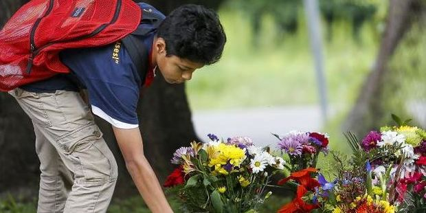 Christopher Martinez, 14, places flowers at a makeshift memorial for his classmate 11-year-old Josue Flores. Photo: AP
