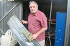 DAMAGE AND LOSS: John Logie with part of the door off the Bay of Islands SPCA's implement shed.