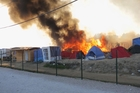 Huts and tents burn at the makeshift camp after violent clashes between Afghan and Sudanese migrants in Calais. Photo / AP