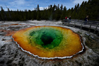 The Morning Glory hot spring in Yellowstone National Park. The colours, due to bacteria, have changed from blue to yellow and green because of coins and debris thrown by tourists. Photo / AFP