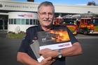 Bryan Barkla holds copies of his book about the history of Whanganui Fire Brigade.   Photo/Bevan Conley