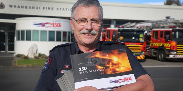Loading Bryan Barkla holds copies of his book about the history of Whanganui Fire Brigade.   Photo/Bevan Conley