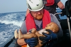 A German rescuer holds the body of a drowned baby off the Libyan coast. Picture / AP