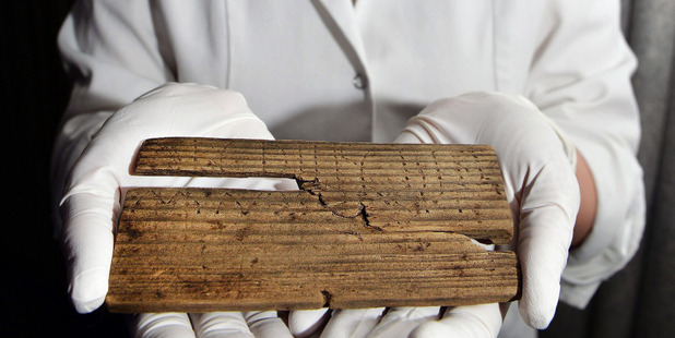 Luisa Duarte, a conservator for the Museum of London, holds a piece of wood with the Roman alphabet written on it in, in London. Photo / AP