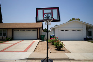 A basketball hoop stands in front of homes with drought-tolerant gardens in Irvine, California. Photo / AP