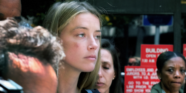 Amber Heard leaves court after giving a sworn declaration that her husband Johnny Depp threw her cellphone at her during a fight. Photo/AP