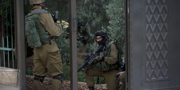 Israeli troops guard the entrance of a house during an army operation at West Bank village of Salem, near Nablus. Photo / AP