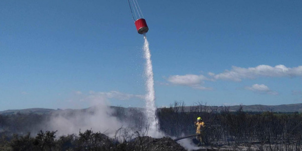 A helicopter helps a firefighter douse the Waitaki River island fire in January. Photo / Supplied