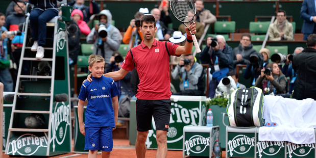 Novak Djokovic celebrates his victory over Tomas Berdych with a ball boy. Photo / Getty Images