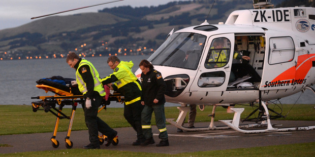 Ambulance officers transfer one of two patients from a helicopter to a waiting ambulance.