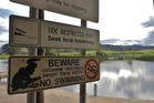 Warning signs at an estuary in the Daintree National Park in Queensland.