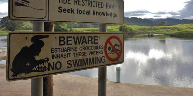 Loading Warning signs at an estuary in the Daintree National Park in Queensland.
