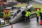 A car ended up over railing on Portal St in Whanganui this morning. Photo/ Stuart Munro