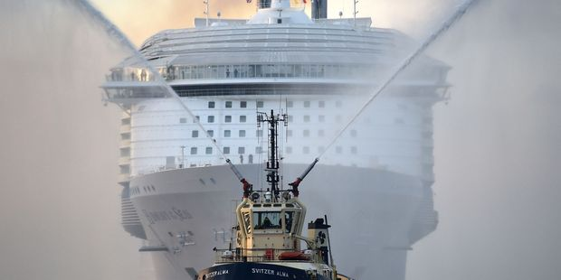 Loading A tug boat leads the way for the world's largest passenger ship, Harmony of the Seas, owned by Royal Caribbean, as it makes her way into Southampton, England. Photo / AP