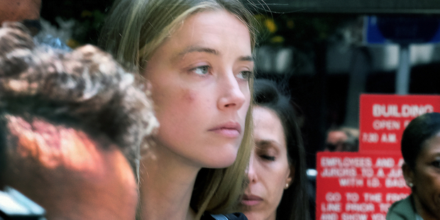 Actress Amber Heard leaves Los Angeles Superior Court after giving a sworn declaration that her husband Johnny Depp threw her cellphone at her during a fight. Photo / AP
