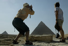 A tourist tries to capture the Sphinx, the Pyramids and his wife in one shot at Giza in Egypt. Photo / Alan Gibson