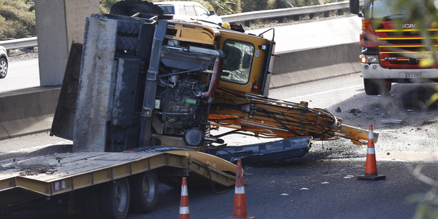 A truck carrying a tall load, a digger, collided with the Penrose Rd overpass on the southbound lanes of Auckland's Southern Motorway. Photo / Nick Reed