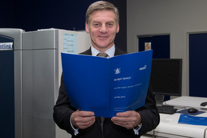 Finance Minister Bill English looking over a copy of the Budget 2016. Photo / Mark Mitchell