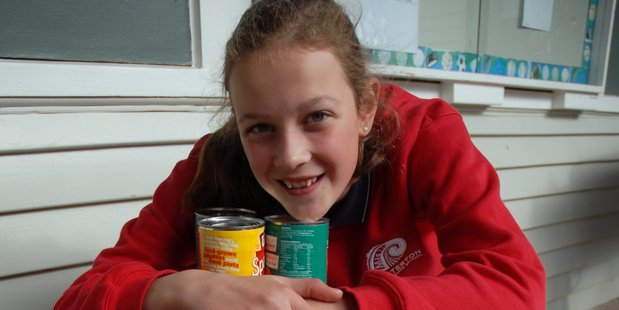 Masterton Intermediate School pupil Millie Matthews, 12, with some of the more than 300 cans she and classmate Leila Ward helped gather for the Masterton Foodbank. PHOTO/NATHAN CROMBIE