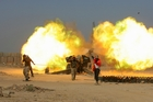 Iraqi security forces and allied Popular Mobilisation forces on the outskirts of Fallujah fire artillery as they battle Isis militants. Picture / AP