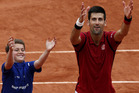 Novak Djokovic, right, teaches a ballboy how to celebrate a victory. Photo / AP