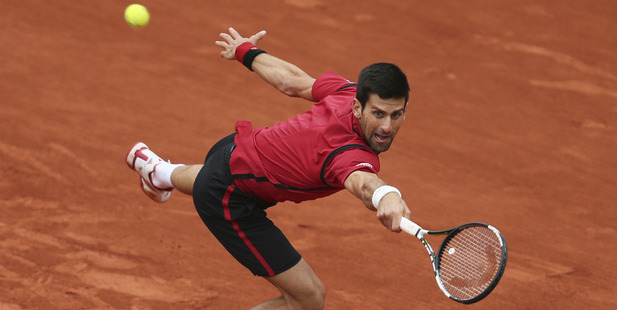 Novak Djokovic stretches to return in the quarterfinal match of the French Open tennis tournament against Tomas Berdych. Photo / AP