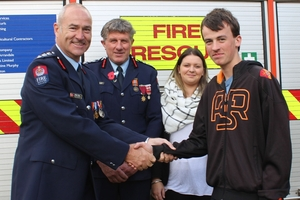 Nigel Hall (left), assistant area commander for the  Fire  Service in the eastern region; Terence Ahern, Norsewood fire chief; with Emily Hullah, 21, and Jorden Seerden, 17. Photo / Christine McKay