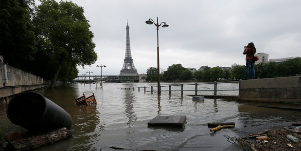 A woman takes photos of the flooded banks of the Seine River in Paris, France. Photo / AP