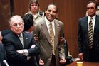 In this October 3, 1995, photo, OJ Simpson, centre, reacts after being found not guilty in the murders of his ex-wife and her friend. Photo / AP