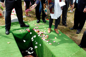 Theresa Carey of San Francisco drops a handful of rose petals into the grave of the 3-year-old girl. Photo / AP