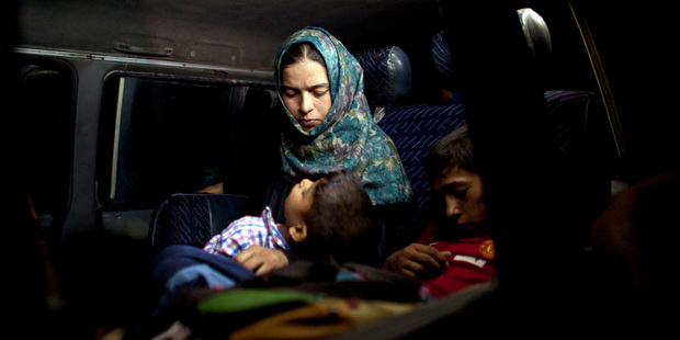 An Iraqi boy sleeps in his mother's arms in a minibus after fleeing Fallujah. Photo / AP