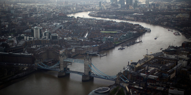 Tower Bridge, centre, and the Canary Wharf business district in the distance as the River Thames flows through London. Photo / AP