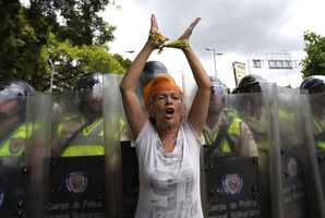 A woman protests in front of a line of Bolivarian National Police during an opposition demonstration in Caracas, Venezuela. Photo / AP