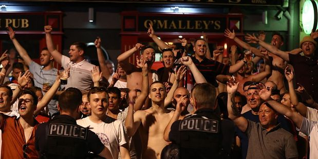 Police officers look on as England fans shout and chant outside a bar ahead of the England v Russia game. Photo / Getty