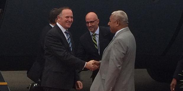 Prime Minister John Key shakes hands with Fiji Prime Minister Frank Bainimarama at Suva Airport. Photo / Claire Trevett