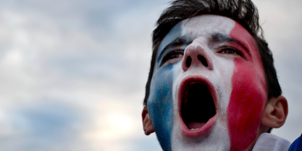A France supporter cheers during the French national anthem prior the Euro 2016 Group A soccer match between France and Romania. Photo / AP.
