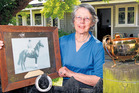 SLICE OF HISTORY: Ann Bary, of Hastings, with a photo of horse Sasanof and the three-handled, three-legged 1916 Melbourne Cup, the first 18-carat gold cup to be awarded to a winner. PHOTO/FILE