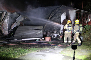 Fire fighters dampen down a house fire on Waiohiki Rd last night.
