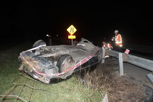 Contractors look over the remains of a car which lost control on State Highway 2 near Masterton.