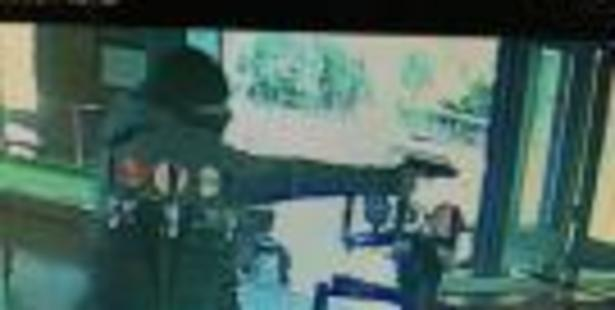 CCTV footage shows a man presenting a firearm in an attempted robbery. Photo / Supplied