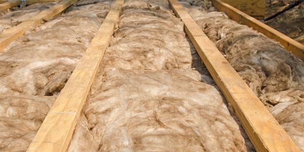 Fiber glass insulation batts unfaced between wood flooring joist cavities. Image / iStock