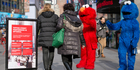 Cookie Monster and Elmo greet tourists in Times Square late in the day, while a sign warns tipping is optional. Photo / iStock