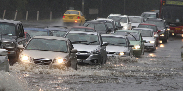 Cars drive through floodwaters on the New South Wales Central Coast. Photo / Getty Images