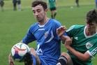 Tauranga City United's Harry Gawrty (blue) battles with Onehunga Sports' Sean Cooper at Links Avenue on Sunday. Photo / Stuart Whitaker