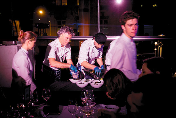 """Peter Gordon and team plate """"Black Splash"""", which guests ate while wearing waterproof bibs. Photo / Dean Purcell"""
